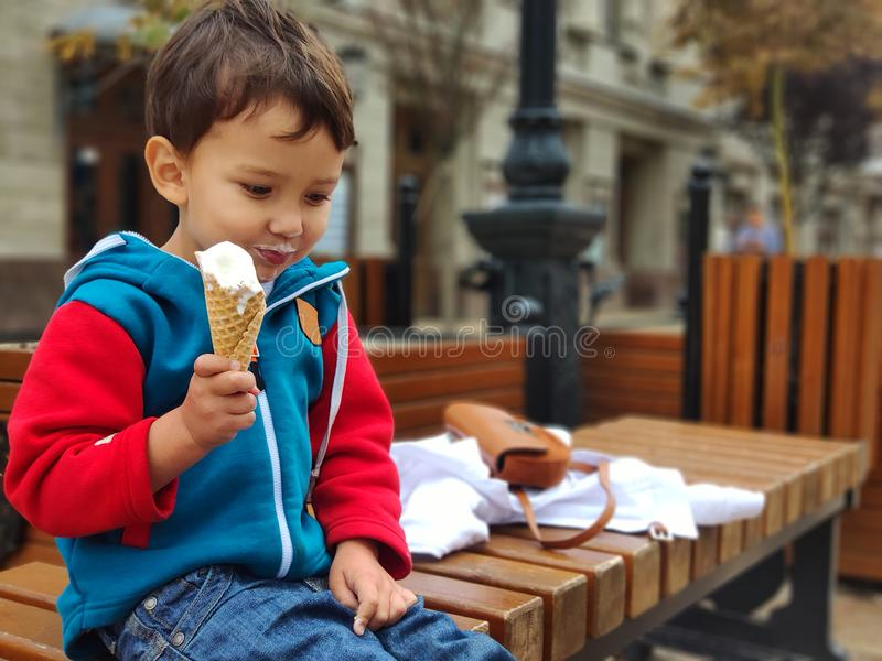 A child in a blue sweatshirt sits on a bench in his hand holds an ice cream cone. Happy child eating waffle ice cream royalty free stock photography
