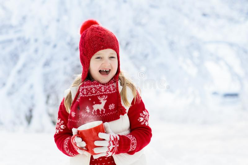 Child drinking chocolate on Christmas in snow stock photo