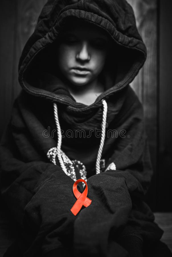 Child with a red heart on a dark background.black and white. stock photography