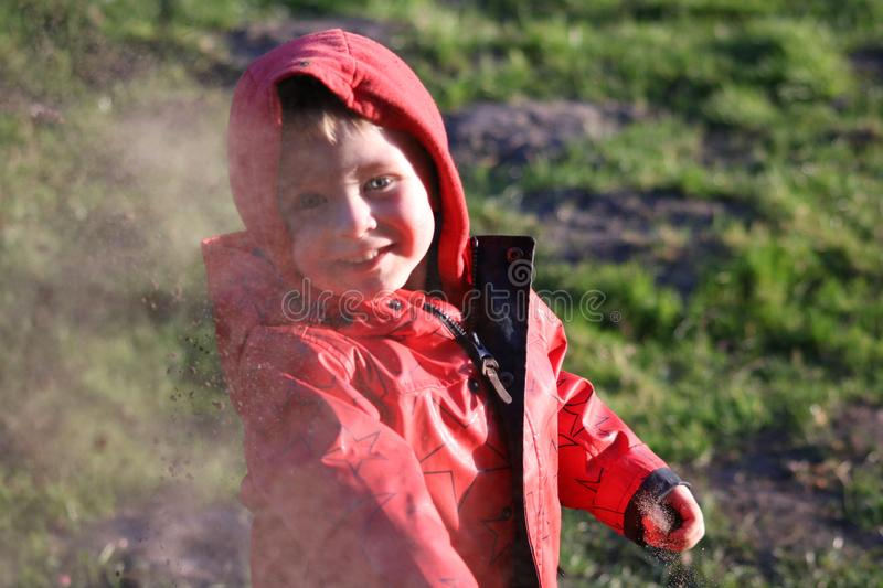 Child in red throwing sand stock image
