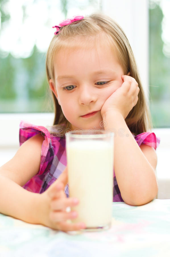 Child refuses to drink milk. Sad little girl refuses to drink a glass of milk royalty free stock photography