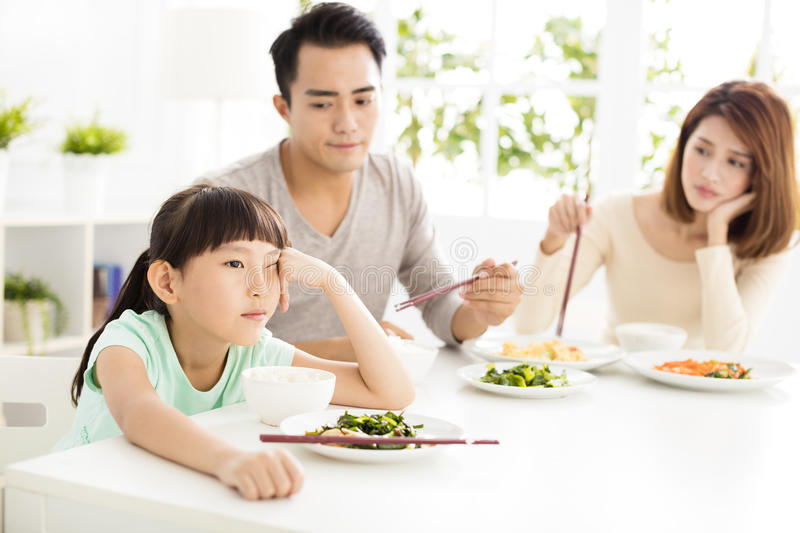 Child refuses to eat while family dinner. Asian child refuses to eat while family dinner stock photos