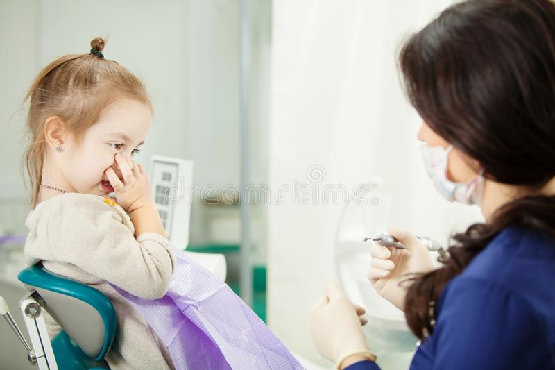 Child refuses to go through medical procedure in dentist office stock photography