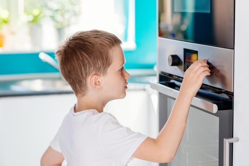 Child regulating temperature of the oven . royalty free stock photos