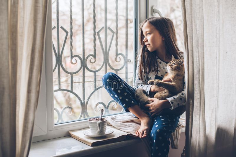Child relaxing with a cat on a window sill royalty free stock photography