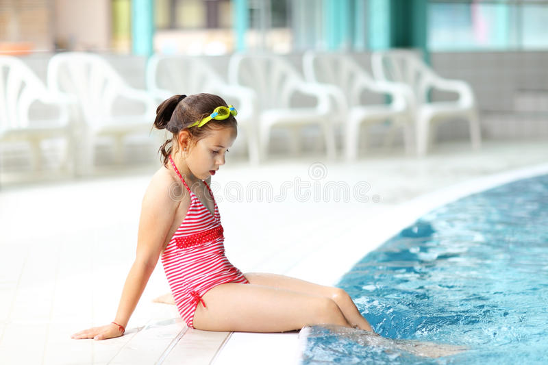 Child relaxing by swimming pool stock photo