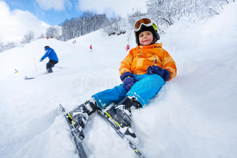 Child rest sitting in snow on side of ski track. Little skier boy rest sitting in snow on ski track smiling and looking at camera royalty free stock images