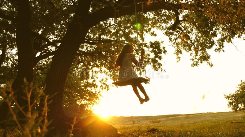 Child rides a rope swing on an oak branch in forest. girl laughs, rejoices. young girl swinging on a swing under a tree. Child rides a rope swing on an oak royalty free stock photos