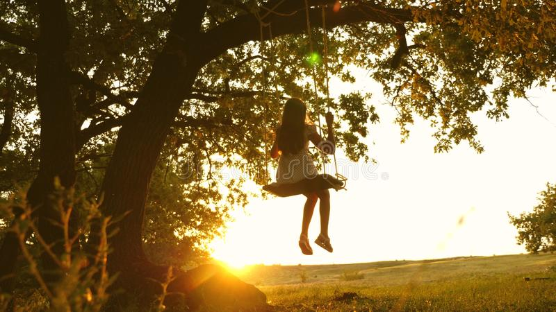 Child rides a rope swing on an oak branch in forest. girl laughs, rejoices. young girl swinging on a swing under a tree. Child rides a rope swing on an oak stock photos