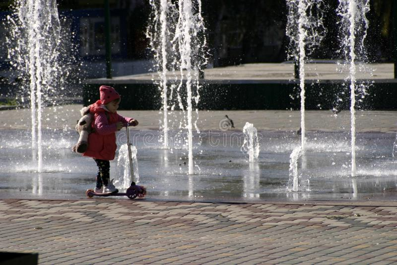 The child rides a scooter at the fountain. royalty free stock photography