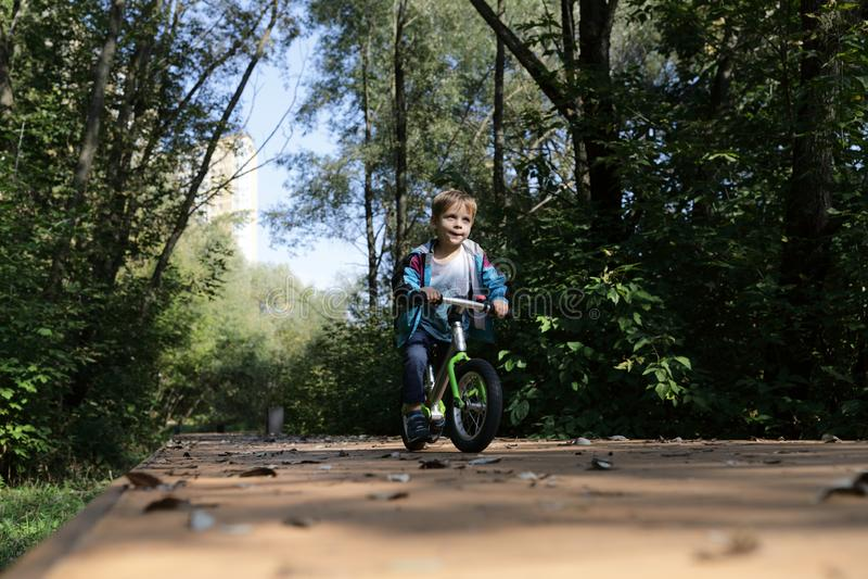 Child riding balance bike stock photography