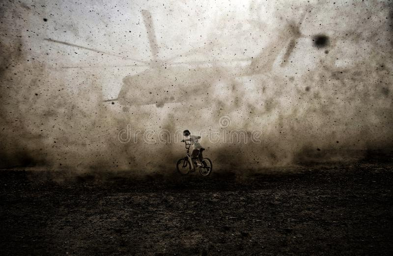 Child riding bike between dust of helicopter stock images
