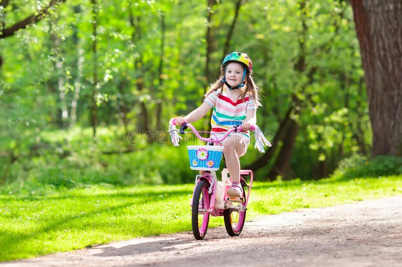Child on bike. Kids ride bicycle. Girl cycling. Child riding a bike in summer park. Little girl learning to ride a bicycle without training wheels. Kindergarten royalty free stock image