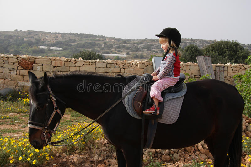 Child riding a horse stock images
