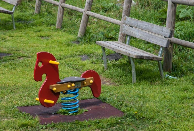 Child Riding Rocking Horse In Playground Stock Image