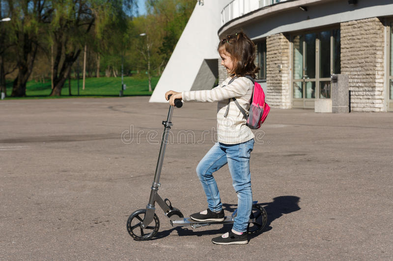 A child is riding a scooter. royalty free stock photo