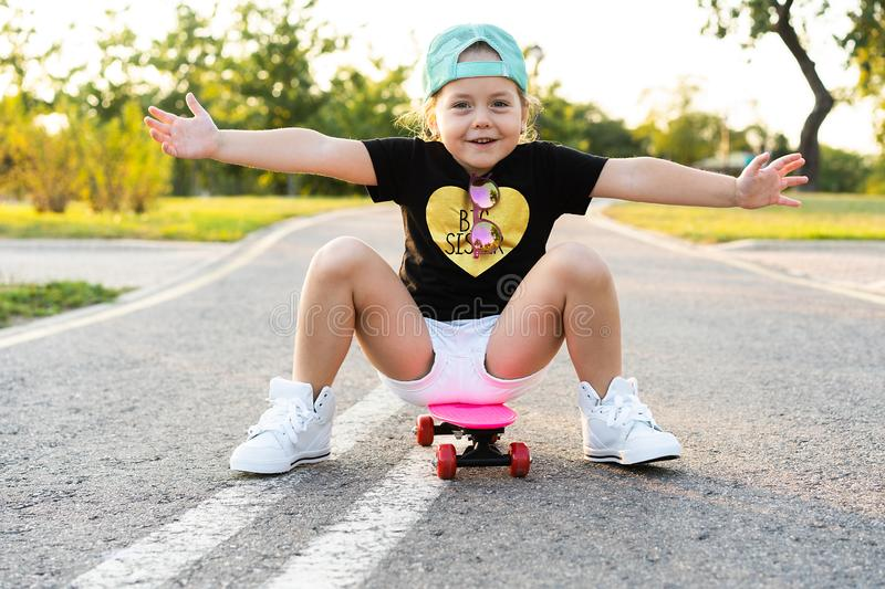 Child riding skateboard in summer park. Little girl learning to ride skate board. Active outdoor sport for school and royalty free stock photography