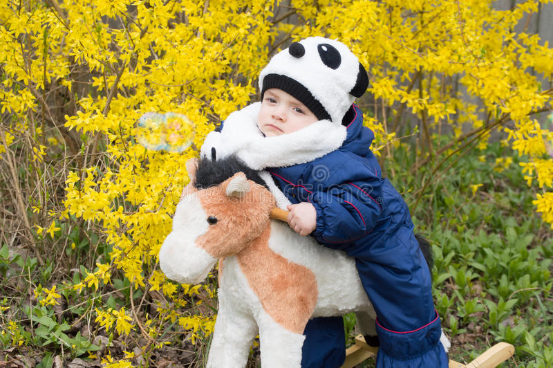 Child riding toy horse stock photography