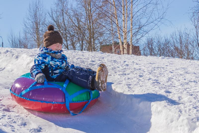 Child is riding tubing winter game. stock photography