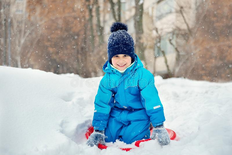 child rolls down a snow hill. Boy sliding down snow hill in winter. Kids play outside. Winter fun concept stock photo