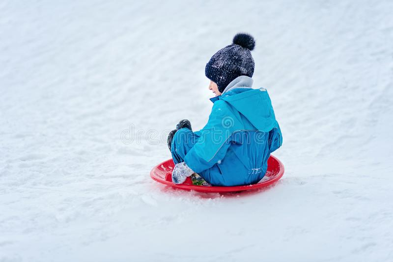 Child rolls down a snow hill. Boy sliding down snow hill in winter. Kids play outside. Winter fun concept. Action active activity caucasian cheerful childhood stock image