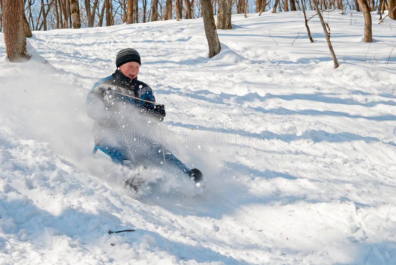 The Child Rolls From The Mountain On A Sled Stock Photography
