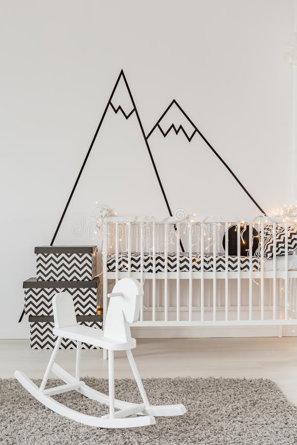 Child room with crib. Well-lighted child room with crib and cockhorse royalty free stock image