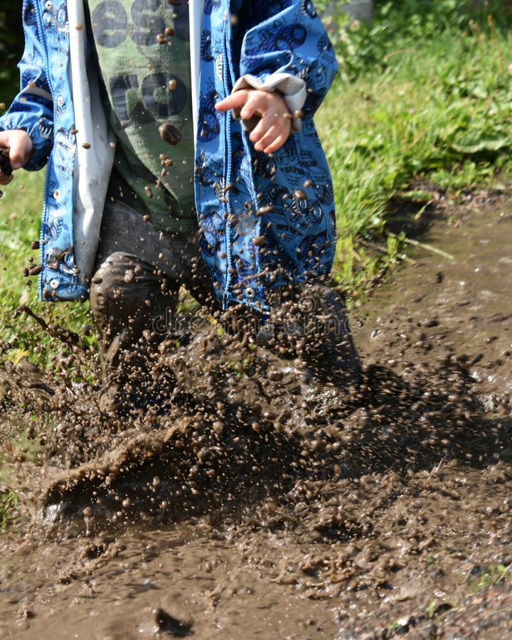 Child in rubber boots playing in mud. mud water splashing and running. funny environmental playground. happy childhood image. stock photo