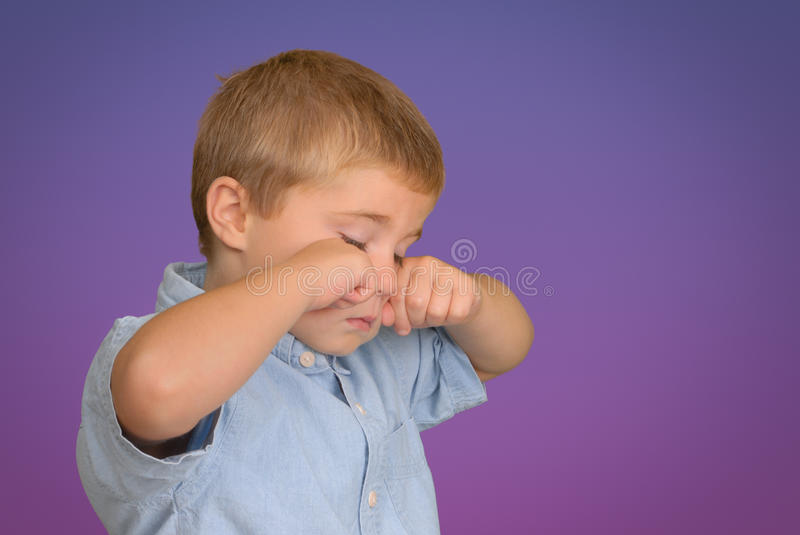 Child Rubbing Eyes. Boy rubbing his eyes because of tiredness or allergies royalty free stock photo