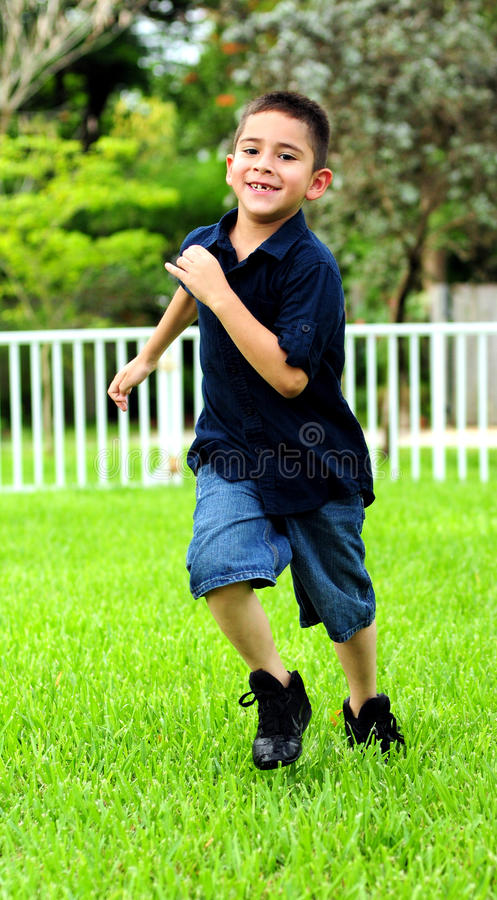 Child running. On grass for exercise and smiling a toothless grin stock photo