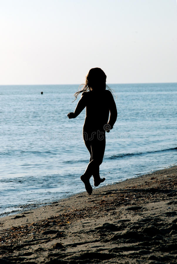 Child running along the beach. Silhouette of a child running along the beach stock image