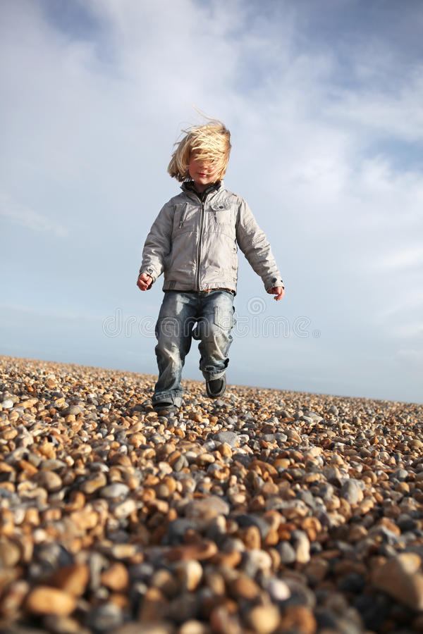 Child running beach freedom. Child running on pebble beach enjoying his freedom. kid with wind in hair by the seaside royalty free stock image
