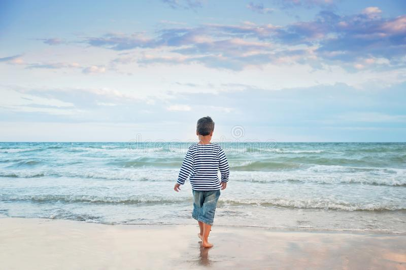 Child running on the beach. Summer vacation. happy kid playing on beach at the sunset time stock images