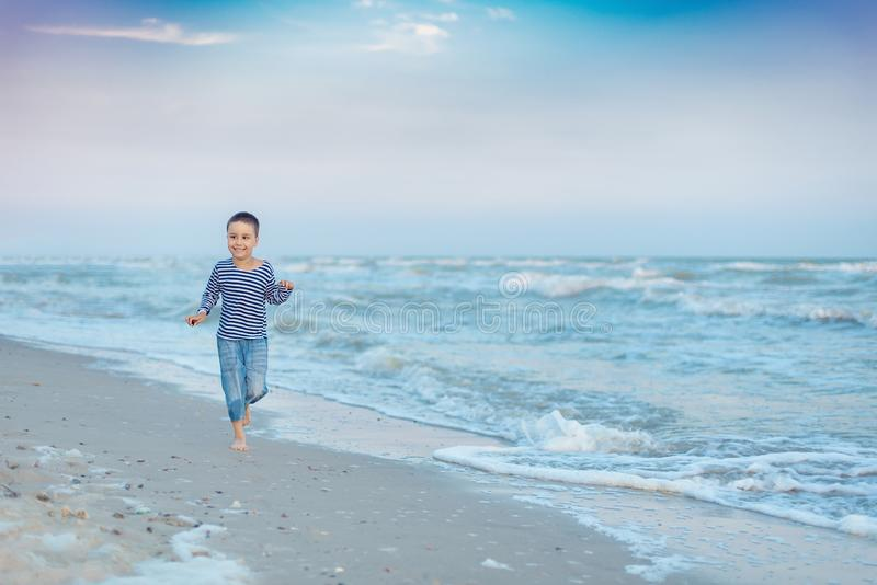 Child running on the beach. Summer vacation. happy kid playing on beach at the sunset time stock photo