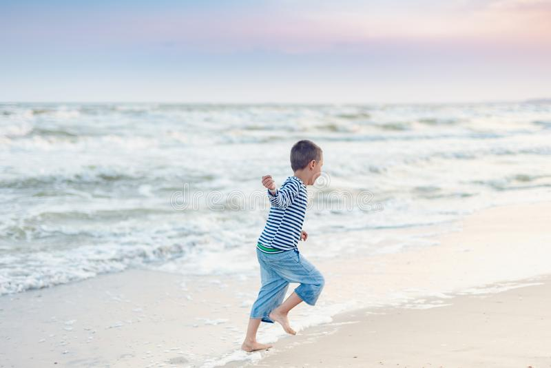 Child running on the beach. Summer vacation. happy kid playing on beach at the sunset time stock photos