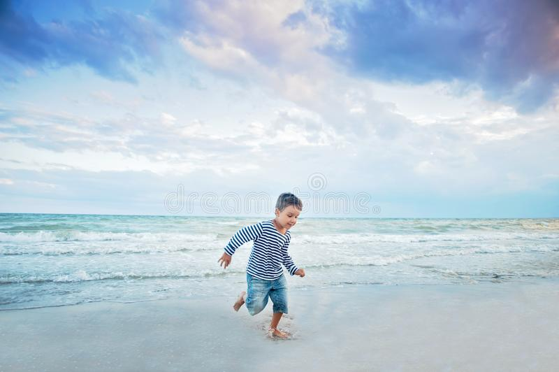 Child running on the beach. Summer vacation. happy kid playing on beach at the sunset time. Boy in a striped T-shirt at the seaside. Child running on the beach stock photos