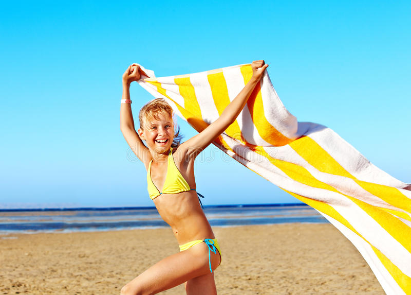 Child running at beach with towel. royalty free stock image