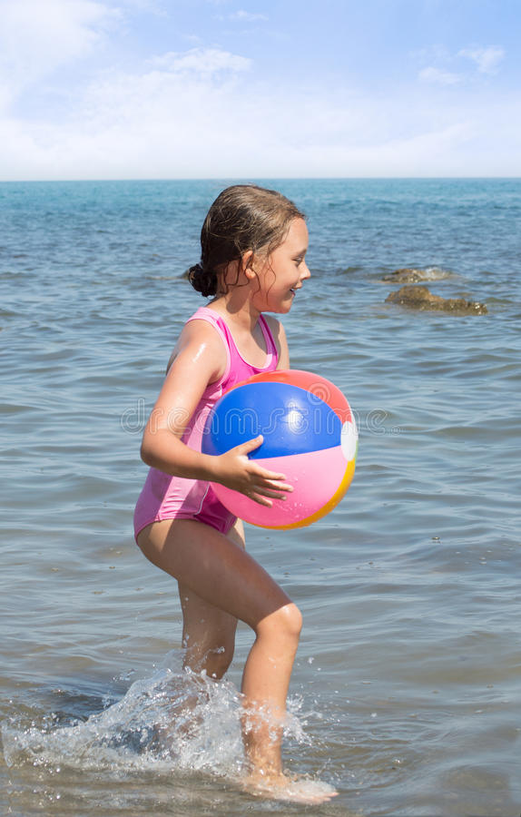 Child running with a colorful ball. On the edge of the beach stock photos