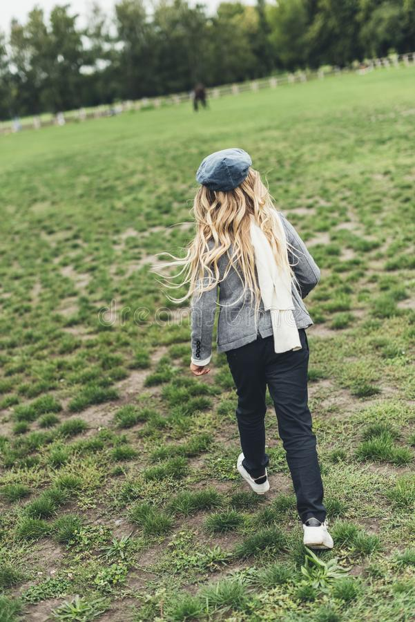 Child running at countryside. Rear view of blonde child running at countryside stock image