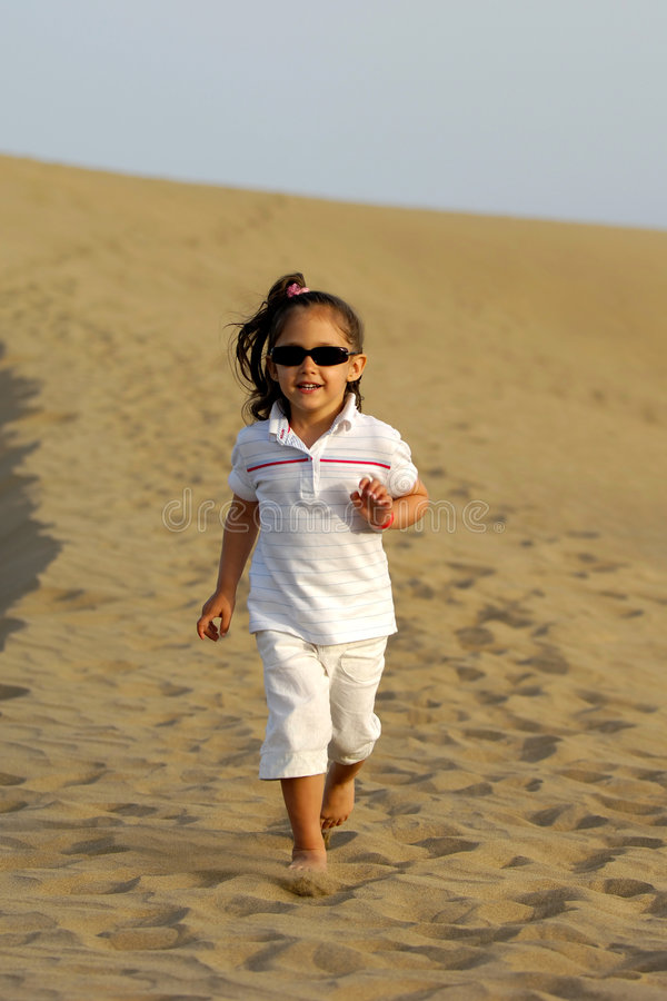 Child running in desert. A happy child is running all alone in the desert stock image