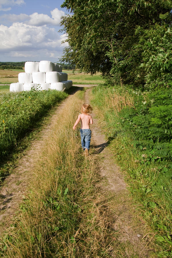 Child running field. Child running down path by field or meadow. summer landscape with small boy royalty free stock photos