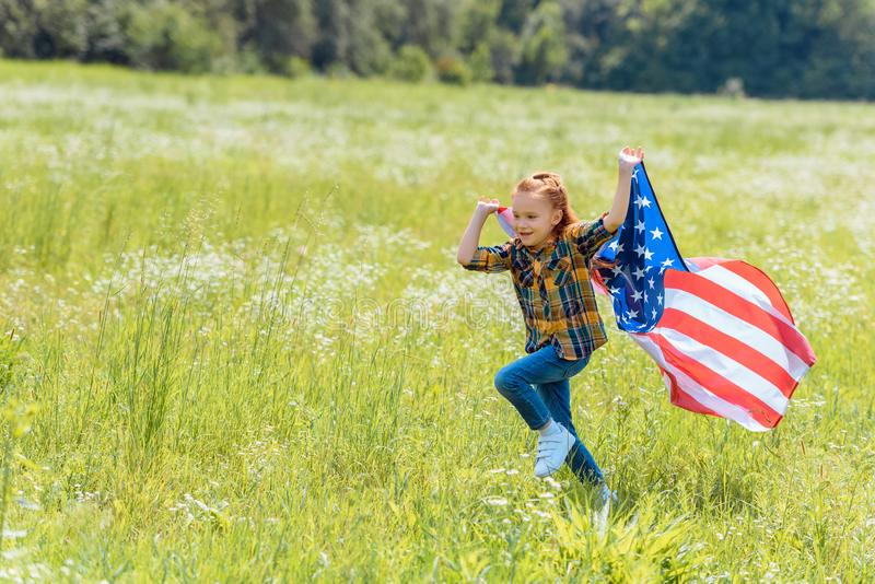 Child running in field with american flag. In hands royalty free stock image