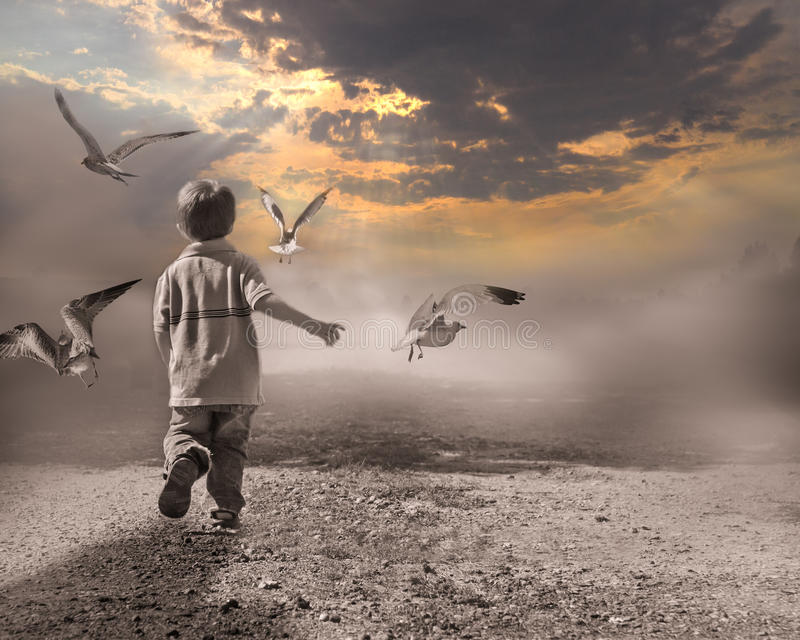 Child running through fog to light of new day. royalty free stock photography