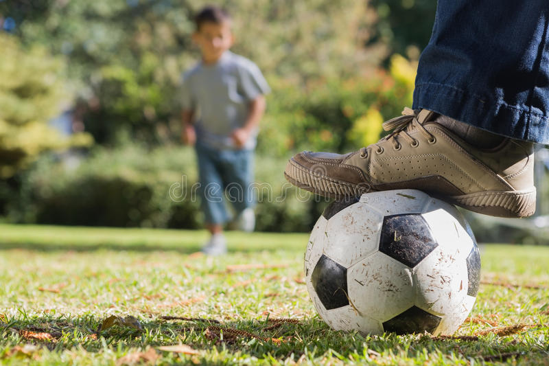 Child running for the football. Under his fathers foot in the park royalty free stock photo