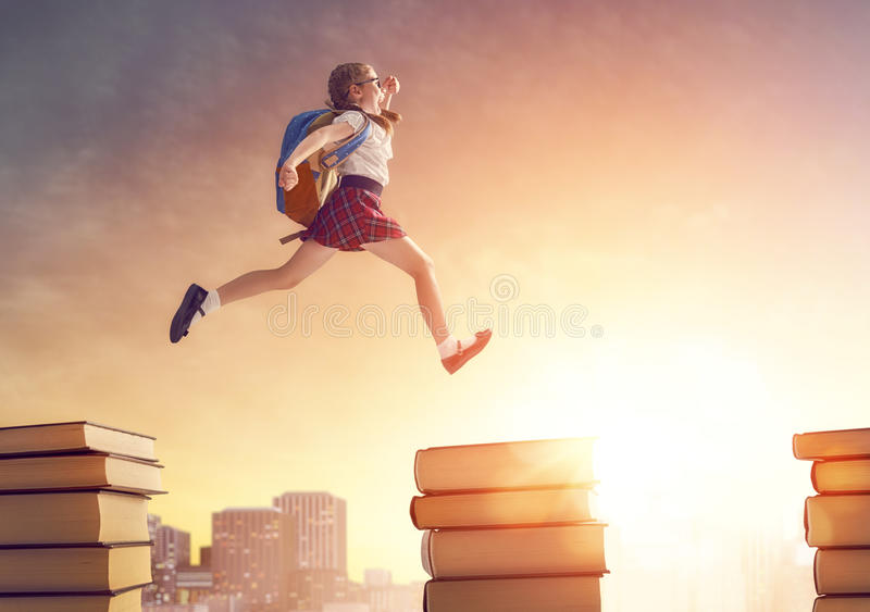 Child running and jumping on books stock photos