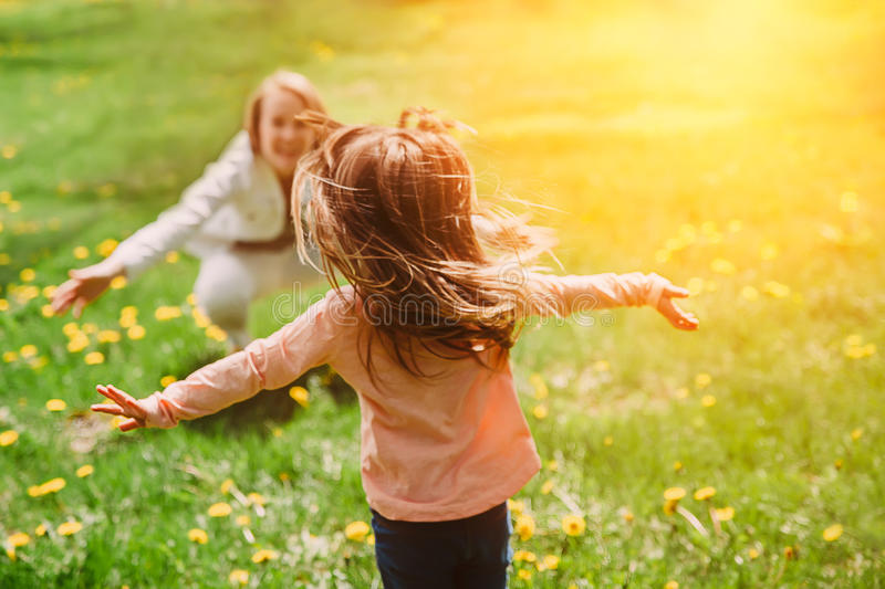 Child running into mother`s hands to hug her. Family having fun in the park. royalty free stock photo