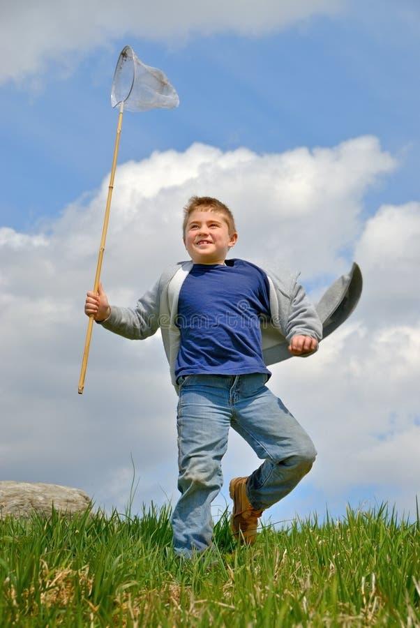 Child Running Outdoors. Boy, running with net outdoors, enjoying nature royalty free stock photo