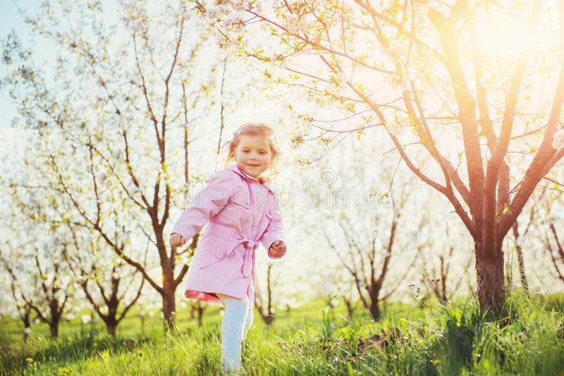 Child running outdoors blossom trees. Colorful toning effect stock image