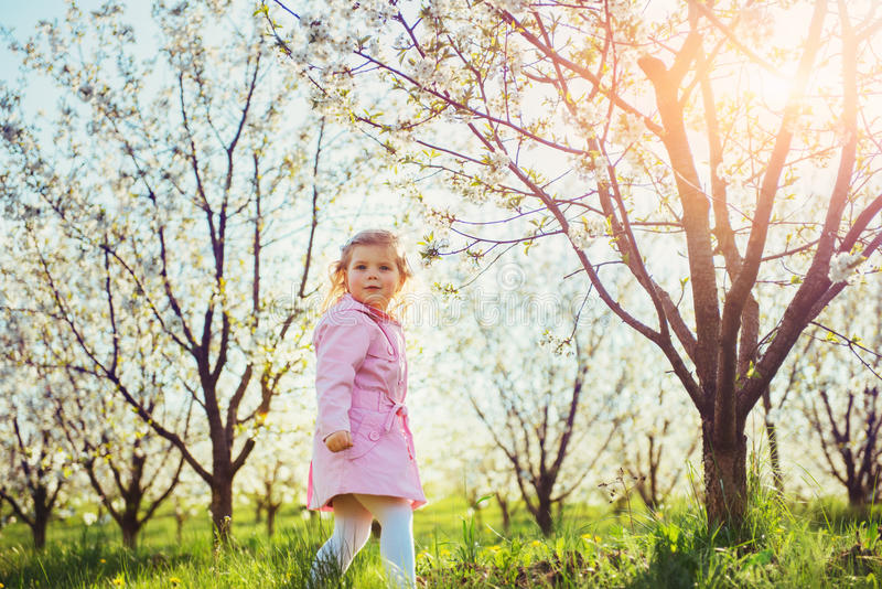 Child running outdoors blossom trees. Colorful toning effect royalty free stock photo