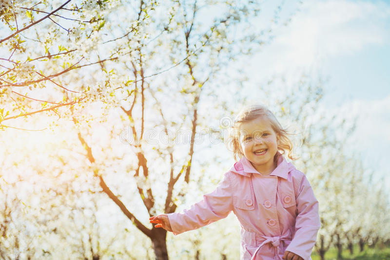Child running outdoors blossom trees. Colorful toning effect royalty free stock photography